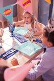 Внимательная девушка дня рождения сидя на таблице и заботливо смотря мальчика стоковые изображения