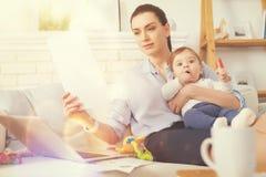 Внимательная коммерсантка сидя дома с ее младенцем Стоковые Изображения RF