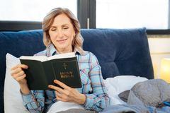 Внимательная любопытная зрелая святая книга чтения женщины стоковые фотографии rf