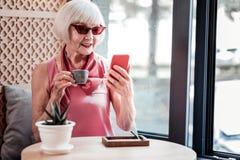 Внимательная седая дама нося стильные солнечные очки пока посещающ кафе стоковые фотографии rf