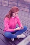 Внимательная симпатичная маленькая девочка сидя на деревянном побережье и проверяя смартфон стоковые фотографии rf