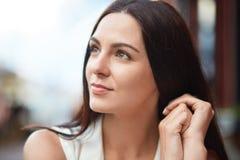 Внимательная сфокусированная молодая женщина с приятным возникновением, темные волосы брюнет, взгляды задумчиво в сторону, предус стоковое изображение
