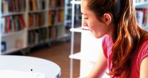 Внимательная школьница делая домашнюю работу в библиотеке сток-видео