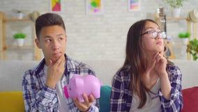 Внимательные молодые пары sian с копилкой в руке сидя на софе видеоматериал