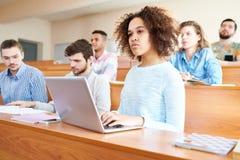 Внимательные студенты слушая к лектору стоковые фотографии rf
