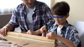 Внимательный мальчик бить молотком ноготь молотком в деревянной планке, отце поддерживая его ребенк стоковая фотография