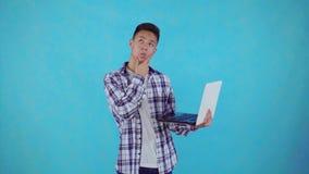 Внимательный молодой азиатский человек с ноутбуком в руке на голубой предпосылке видеоматериал