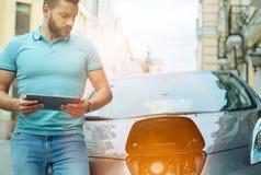 Внимательный молодой человек смотря его электрический автомобиль стоковое фото