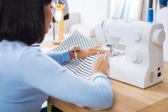 Внимательный портной шить striped часть ткани на швейной машине стоковое фото