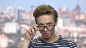 Внимательный предназначенный для подростков мальчик регулируя его eyeglasses сток-видео