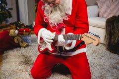 Внимательный Санта Клаус играя гитару Стоковое Фото