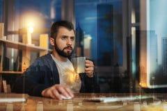 Внимательный человек держа чашку пока работающ перед его компьютером Стоковые Изображения