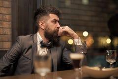 Внимательный человек сидя на таблице с рюмкой в бар-ресторане стоковые изображения rf