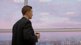 Внимательный человек с кофе, который нужно пойти посмотреть через окно на красивых выравниваясь небе и городе сток-видео