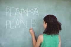 Внимательная школьница претендуя быть учителем в классе стоковая фотография rf