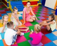 Внимательные дети сидя с учителем и имея переговор стоковые фото