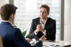 Внимательный бизнесмен слушая к duri делового партнера говоря Стоковое фото RF