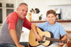 Внук деда уча для того чтобы сыграть гитару Стоковое Изображение