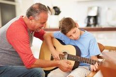 Внук деда уча для того чтобы сыграть гитару Стоковая Фотография RF