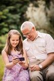Внук показывает smartphone деда Стоковая Фотография