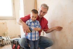 Внук учит от его деда обозревает метр Стоковое фото RF