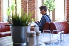Внутренние таблицы и стулья кафа Фотограф человека сидя на таблице E E 06 02 2019 стоковое изображение rf