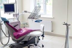 Внутренность зубоврачевания, фиолетовый стул для пациента и оборудование стоковые фотографии rf
