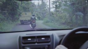 Внутренность moving автомобиля в сельской дороге с катанием велосипеда и тележки перед им сток-видео