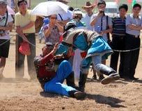 ВНУТРЕННЯЯ МОНГОЛИЯ, КИТАЙ - 14-ОЕ ИЮЛЯ: Монгольские молодые человеки wrestling в в степи около Hohhot Стоковая Фотография RF