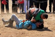 ВНУТРЕННЯЯ МОНГОЛИЯ, КИТАЙ - 14-ОЕ ИЮЛЯ: Монгольские молодые человеки wrestling в в степи около Hohhot Стоковое фото RF