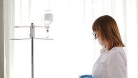 Внутривенный потек регулируя в светлой комнате хирургии, капании вливания Пациент хирурга работая в операционной сток-видео