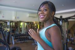 Внутри помещения портрет спортзала молодой разминки привлекательного и счастливого черного Афро-американского sporty третбана тре стоковое фото rf