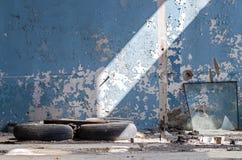 Внутри старого покинутого промышленного здания, фабрика Стена с слезать голубую краску Используемые автошины, колеса Много различ Стоковые Фото