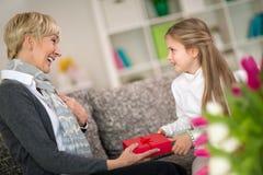 Внучка давая подарок к ее бабушке стоковое фото