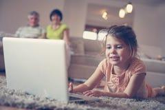 Внучка используя компьтер-книжку в живущей комнате Стоковая Фотография RF