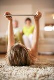 Внучка используя таблетку в живущей комнате Стоковое Изображение