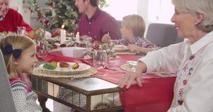 Внучка и бабушка играя с заполненным северным оленем игрушки как семья сидят вокруг таблицы наслаждаясь едой рождества совместно сток-видео