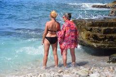 Внучка и бабушка стоя в море, наслаждаются теплой погодой, солнцем, морем и компанией одина другого Стоковые Изображения