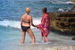 Внучка и бабушка стоя в море, наслаждаются теплой погодой, солнцем, морем и компанией одина другого Стоковые Изображения RF