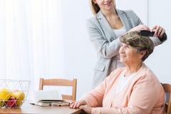 Внучка расчесывая волосы бабушки стоковая фотография rf