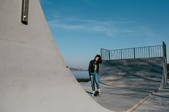 Внушительная девушка скейтбордиста с скейтбордом внешним на skatepark Skatebord на городе, улице Холодное, смешное Tenager Стоковые Фотографии RF