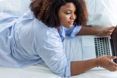 Внушительная задумчивая девушка смотря монитор ноутбука пока лежащ на кровати стоковое изображение rf