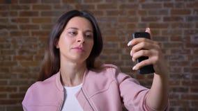 Внушительная кавказская женщина висит на видео- звонке, смотрит ее камеру телефона и говорит холодок, красный кирпич видеоматериал