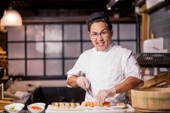 Внушительный шеф-повар hansone смотрит камеру пока варящ суши стоковые фото