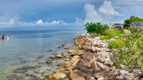 Вода бирюзы голубого неба Tampa Bay Флориды около камней и деревьев берега русых стоковое фото