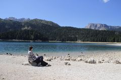 Вода бирюзы озера, соснового леса и гор Оглушать предпосылка с туристом девушки природы сидя на пляже стоковая фотография rf