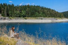 Вода бирюзы озера, соснового леса и гор Оглушать предпосылка с туристом девушки природы сидя на пляже стоковое фото rf