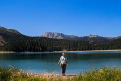 Вода бирюзы озера, соснового леса и гор Оглушать предпосылка с ликованием девушки природы туристским на пляже стоковая фотография