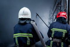 Вода брызга пожарных Дым и buiding после огня Стоковая Фотография
