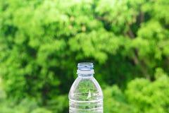 Вода бутылки сделала к пластмассе на предпосылке неба и дерева расплывчатой Используя обои для пакета или продукта, освежая изобр Стоковое Фото